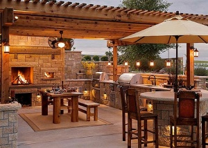 Captivating-Outdoor-Kitchen-with-Stone-Fireplace-Wooden-Dining-Table-Good-Lighting-and-Patio-Umbrella