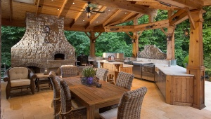 Fancy-Outdoor-Kitchen-Design-with-Wooden-Dining-Table-Wicker-Chairs-and-Stone-Fireplace
