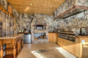 Outdoor-Kitchen-Design-with-Natural-Stone-Wall-Fireplace-Teak-Wood-Cabinets-and-Granite-Worktop