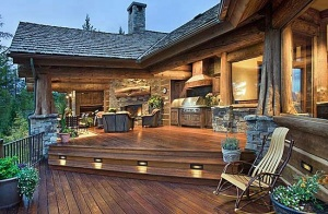 Exterior, horizontal, rear deck overall toward fireplace and built in bar-b-que at twilight, Witt residence, Whitefish, Montana; High Country Builders; The Old World Cabinet Company